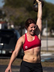 Crystal Moel, of Cape Coral, uses a kettlebell as part