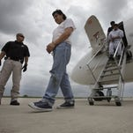 In May 25, 2010, Mexican immigrant Javier Castillo, center, walks on the tarmac after he was flown from Chicago to Harlingen, Texas, for deportation.