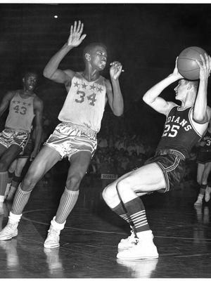Bobby Plump (right) of Milan High School and his Indian teammates defeated Crispus Attucks in the finals of the Indianapolis semifinal basketball tourney on March 13 1954. Oscar Robertson is the player at left in the background and in center is Attucks' Willie Mason.
