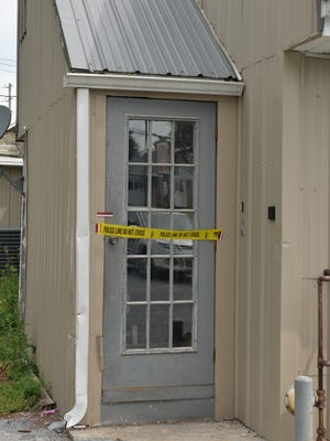 Police tape marks what is believed to be the entrance to the second-floor apartment above the Horseshoe Pike Gun Shop, located at 2703 Horseshoe Pike in South Londonderry Township and the scene of a homicide shortly before 1 a.m. Sunday, July 3, 2016.