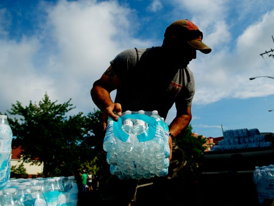 Chris Bryant, father of Nick Bryant, helps unload cases of water at Knox Area Rescue Ministries, 418 N Broadway, in Knoxville, Tennessee on Saturday, July 8, 2017. Since the age of 10, Nick Bryant, now 15, has been asking for cases of water instead of presents to donate to KARM.