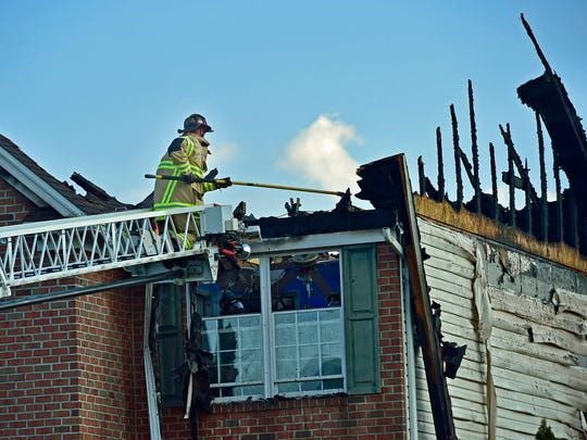 A firefighter works from a ladder at a home the caught fire Tuesday, September 6, 2016 at 13142 Whispering Spring Drive, Antrim Township. The family was not home when the fire started and there were no injuries, according to Rescue Hose Fire Chief Kevin Barnes.