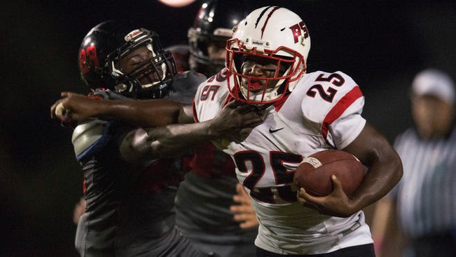 Port St. Lucie's Emmanuel Noel runs the ball as South Fork's Rod Dames tries to make the tackle in the first half of their game at South Fork High School on Friday in Tropical Farms. To see more photos, go to TCPalm.com.