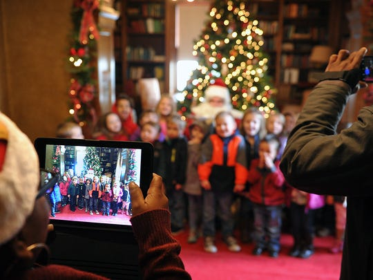 Children from Youth YMCA have their photos taken with Santa Claus during the Santa House tour at the Kell House Museum Friday morning.