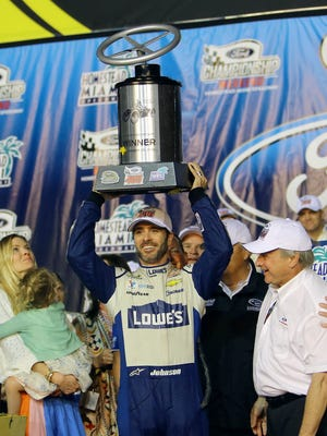 Jimmie Johnson holds up the race winners trophy.
