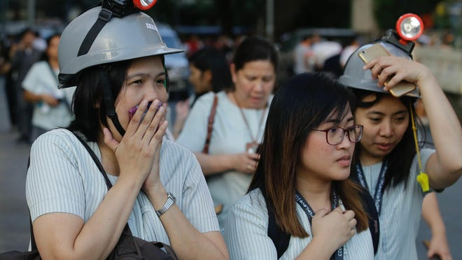 Wearing protective helmets, employees evacuate their office building following an earthquake in Manila, Philippines on Monday, April 22, 2019. The U.S. Geological Survey says the magnitude 6.3 quake struck northwest of Manila near the town of Gutad on Luzon island.