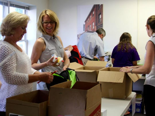 Tanya Benosky, center, of the Burlington Boys & Girls Club passes glue to be added to the backpacks during the packing at the COTS office.