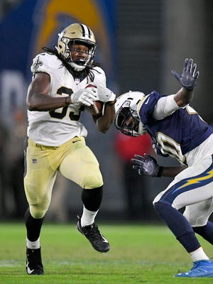 New Orleans Saints running back Trey Edmunds, left, runs past Los Angeles Chargers defensive end Chris McCain during the second half of a preseason football game Sunday. The Saints won 13-7.