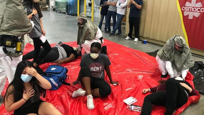 Emergency medicine physician residents from FAU check volunteers during a simulation drill at a warehouse in Coconut Creek.
