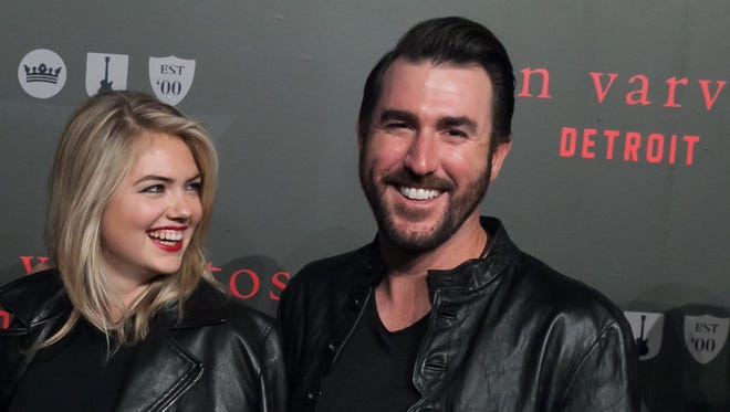 Model Kate Upton and Detroit Tigers pitcher Justin Verlander, right, pose on the black carpet during the grand opening celebration of the Varvatos Detroit store April 16, 2015.