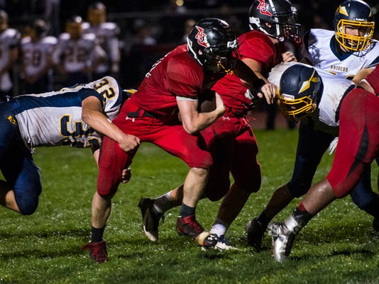 Annville-Cleona's Will Langan tries to shed Elco's Ryan Rolon as Elco defeated Annville-Cleona 40-39 in overtime at Annville-Cleona High School on Thursday, October 1, 2015.