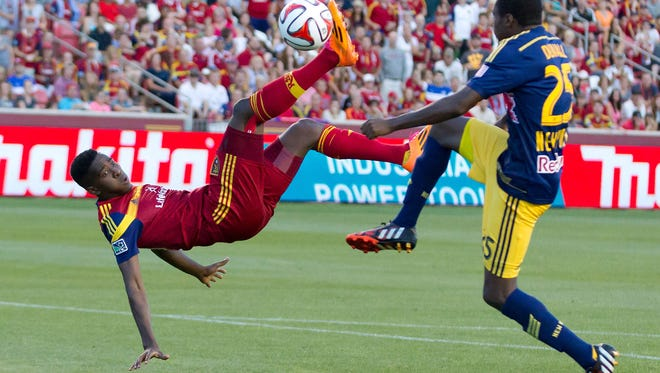 Real Salt Lake forward Olmes Garcia bicycle kicks the ball in front of New York Red Bulls defender Chris Duvall during the second half at Rio Tinto Stadium. The match ended in a 1-1 tie.