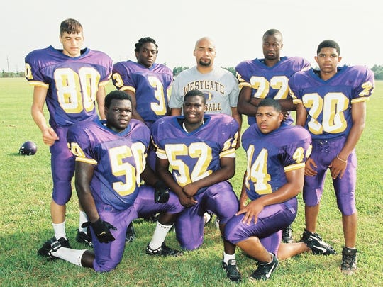 Westgate coach Oliver Winston with some members of the original Tigers' defense in the program's first season of 1999.
