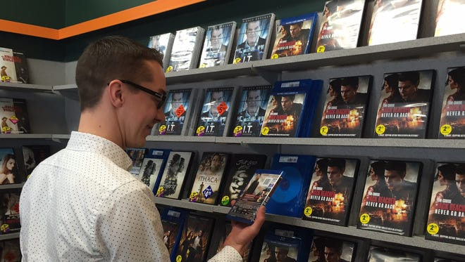 Highland Ventures district manager Matt Hill looks at a new release selection at Family Video in Elsmere.