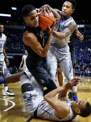 University of Memphis teammates  Jimario Rivers (bottom) and Markel Crawford (right) battle University of Central Florida guard  A.J. Davis (left) during first half action at the FedExForum.
