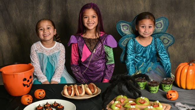 From left, Juliana Cruz, 6, Mylie Butters, 7, and Catalina Cruz, 7, stand with an array of cute and scary Halloween snack projects in Agana on Oct. 8.