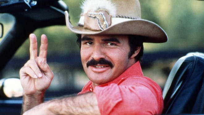 """Burt Reynolds is seen behind the wheel of his iconic Trans Am in """"Smokey and the Bandit"""" (1977)."""