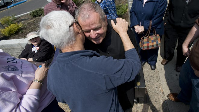 Father Jerome Romanowski of St. Mary's Church in Malaga is hugged by a parishoner as they protest the closing of their church outside the Camden Diocese offices in downtown Camden in 2008.