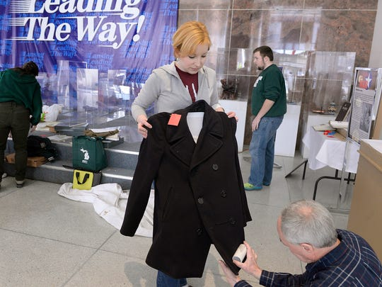 Valerie Marvin and Bob Mainfort clean off a Vietnam-era U.S. Navy peacoat as they help set up the huge Lansing Goes to War exhibit in the lobby at Lansing City Hall. The exhibit features many items connected to the service of Lansing-area veterans.