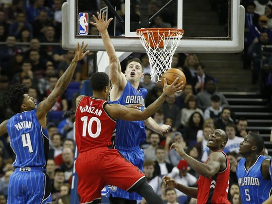 Toronto Raptors guard DeMar DeRozan, center, goes for the basket as Orlando Magic's Jason Smith defends during the first half of an NBA basketball game, at the O2 arena in London, Thursday, Jan. 14, 2016. Raptors won the game 106-103. (AP Photo/Alastair Grant)