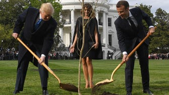 First lady Melania Trump watches Presidents Trump and Macron plant a tree on April 23, 2018.