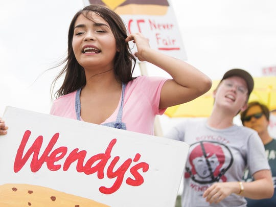 Pamela Vazquez, 22, joins more than 30 farmworkers, students and Southwest Florida residents protesting on Sunday outside Wendy's at Six Mile Cypress Parkway and U.S. 41 in Fort Myers. The protest, organized by the Coalition of Immokalee Workers (CIW) and the Student Farmworker Alliance, calls for Wendy's to join the Fair Food Program (FFP). FFP is a workplace monitoring initiative that seeks humane wages and working conditions for the workers who pick fruits and vegetables in seven states along the east coast. Wendy's is the only major fast food company that has not committed to FFP. On July 19, the CIW will protest in New York at the office of Wendy's Board Chair Nelson Peltz.