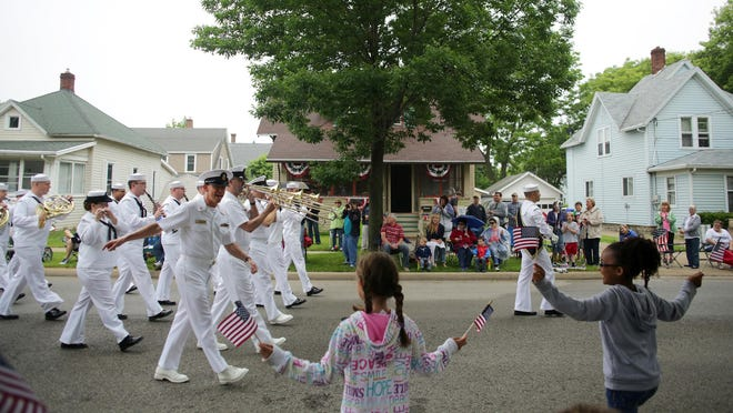 Master Chief Musician Todd Smeltzer waves and talks to the crowd as the Navy Band Great Lakes performs during the 65th Annual Appleton Flag Day Parade in Appleton on  Saturday. This year's parade honored the U.S. Navy.