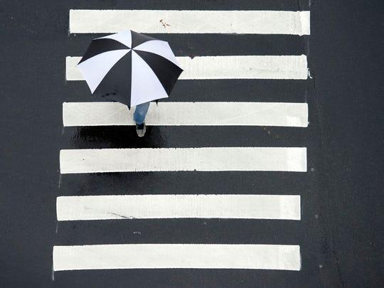 An umbrella-wielding pedestrian at the intersection