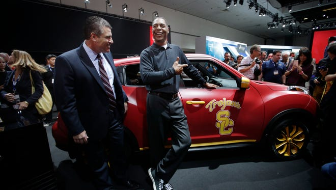 Fred Diaz, Nissan North  America senior vice president, left, joins 1981 Heisman trophy winner Marcus Allen in front of the 2015 Nissan Juke at last month's Los Angeles Auto Show