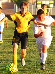 Alamogordo's Lucas Burch moves a ball down field while being pursued by Ruidoso's Jose Garcia.