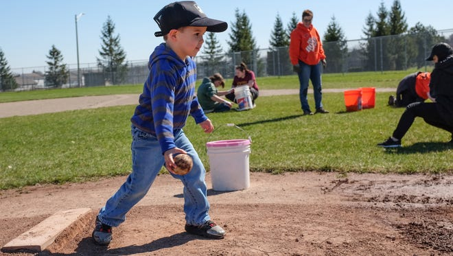 Gavin Pearl, 3, tries out the pitcher's mound at the Eastern High School baseball field Saturday, April 8, 2017. A group of volunteers, as part of a Day of Service, from MSU, the City of Lansing, Eastern, and The Home Depot descended on the field to get it ready for the first home game on Wednesday. Projects included raking leaves, aerating the grass, painting and making some renovations to the dugouts.