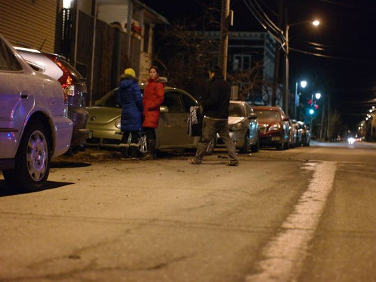Burlington residents look over damaged cars late Thursday from a hit-and-run in the city near the intersection of North Avenue and North Street. A driver was apprehended near UVM.