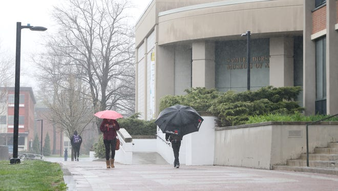 Students walk to and from class on a rainy day at SUNY New Paltz on April 25, 2018.