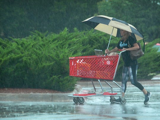 A woman tries to stay dry in the pouring rain Friday morning as a storm system moved slowly through the North Texas area.