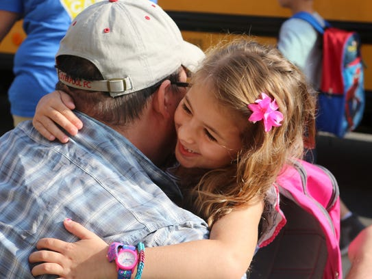 Kindergartner Savannah Ayton hugs her father, Jordan
