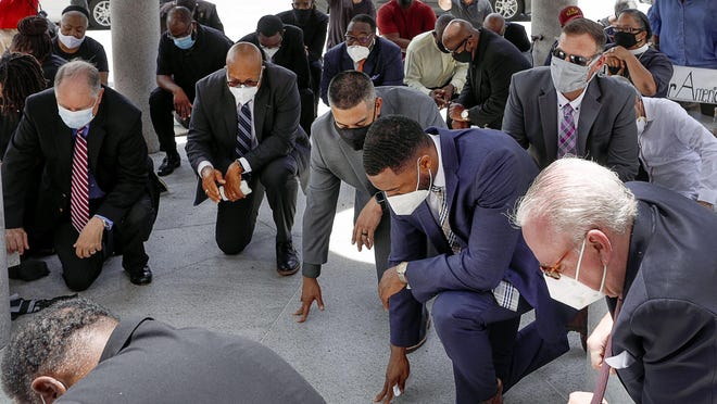Members of the Palm Beach Clergy Alliance take a knee in protest against racial injustice outside the Palm Beach County Courthouse, June 5, 2020.