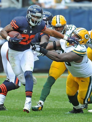 Packers defensive lineman Mike Daniels (76) gets stiff armed by Bears running back Matt Forte (22) at Soldier Field.