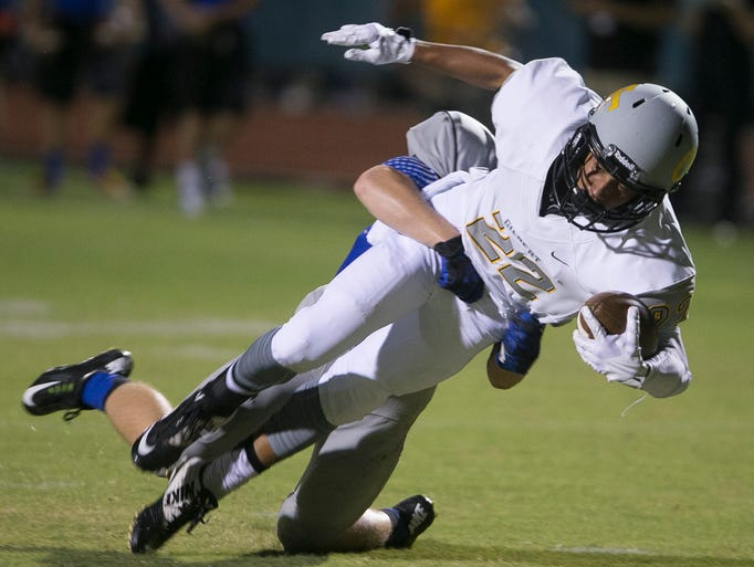 Gilbert wide receiver Rico Yanez carries a Mesquite defender into the end zone for a touchdown in the second quarter of a game at Mesquite High School in Gilbert, Ariz. on Thursday, Aug. 28, 2014.
