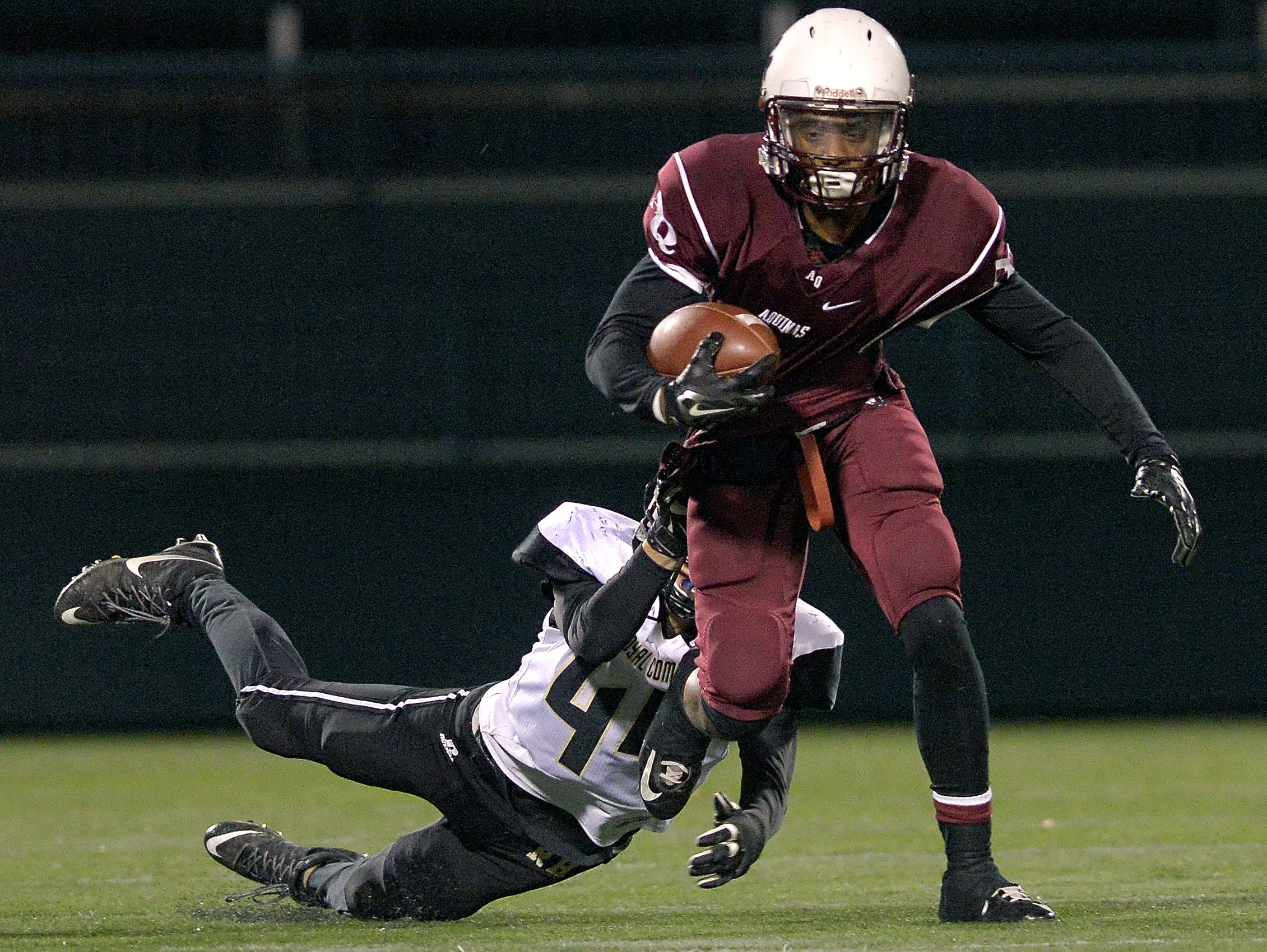 Aquinas earnest edwards right tries to break the grasp of rush