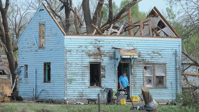 A woman salvages items May 12 from a house that was damaged in the tornado that struck Delmont.