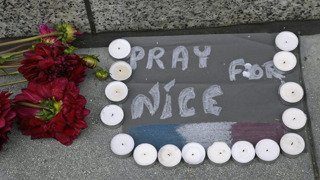 Flowers and candles are left following the attacks in Nice outside the entrance to the French Consulate Friday, July 15, 2016, in San Francisco. Scores of people were killed Thursday night after a Tunisian man drove a truck through crowds celebrating Bastille Day in Nice. (AP Photo/Eric Risberg)