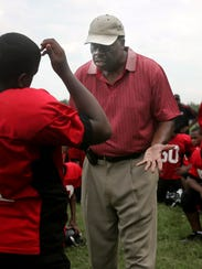 Football coach Maurice Fitzgerald instructs a Smithson