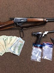 Weapons and suspected drug money allegedly found at Purnell Collins home.