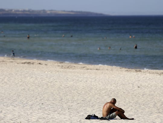 A beachgoer sits in the sun on Glenelg Beach in Adelaide,