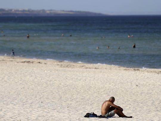 A beachgoer sits in the sun on Glenelg Beach in Adelaide, Australia, Jan. 24, 2019.