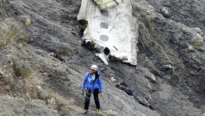 A search and rescue worker passes debris and wreckage at the crash site of the Germanwings Airbus A320 on March 25 in the French Alps near Seyne. The aircraft with 150 people on board crashed March 24 during a flight from Barcelona to Duesseldorf, Germany.
