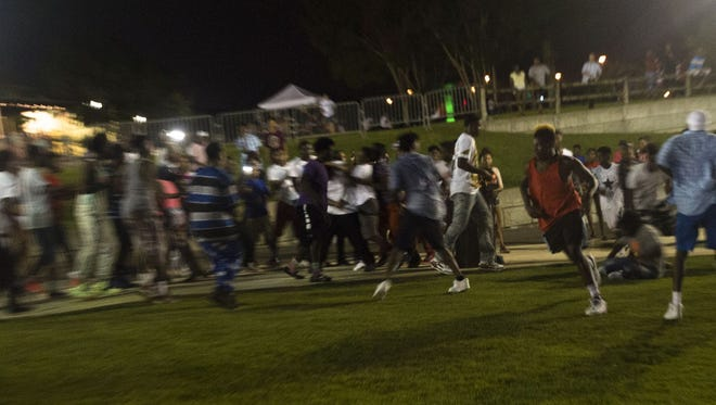 A fight breaks out at Riverfront Park in Montgomery, Ala., on Saturday, July 18, 2015. A person threatened to shoot people at Riverfront Park on Facebook earlier. Montgomery Police made an immediate arrest after the shots were fired.