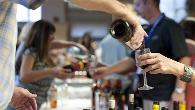 Wine sampling at Bank of the Sierra during Taste of Downtown Visalia on Tuesday, October 7, 2014.