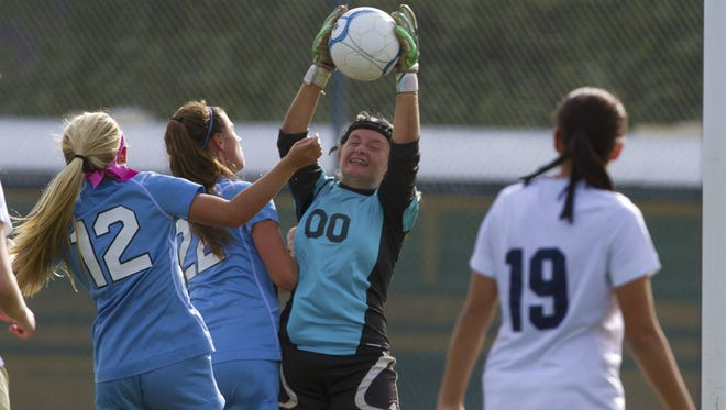 Freehold Township goalie Kaela Chadzuito pulls in a shot on goal as she's crowded by Freehold Boro's Emma Smith and Carly Columbe. Freehold Township Girls Soccer vs Freehold Boro in Freehold Boro on September 25, 2015