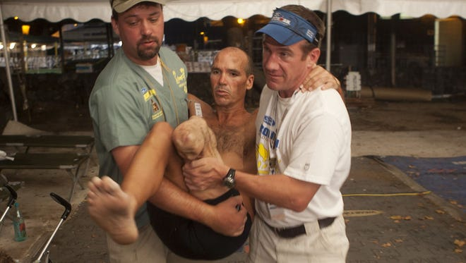 Double amputee Jason Gunter is carried to an awaiting vehicle after a stay in the med tent at the Hawaii Ironman in 2009. He collapsed at mile 22 of the run. On the right is his handler Mike Lenhart. He has a chance to compete again in 2015.